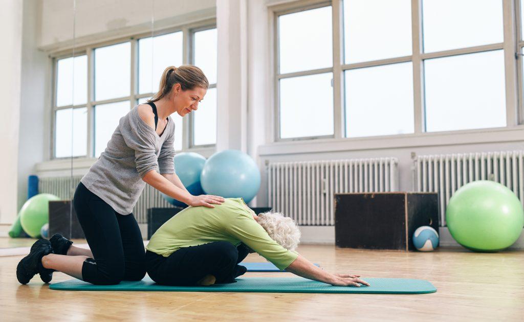 yoga teacher assisting a student